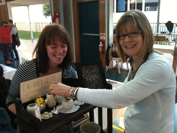 A lovely customer purchasing a gold lustre bud vase from Handmade Redcliffe