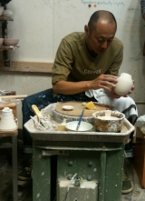 Preparing the teapot body for the strainer and spout attachment.