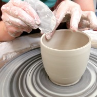 Attending to the rim of a cup while throwing